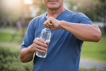 Asian senior male holding bottle of water.