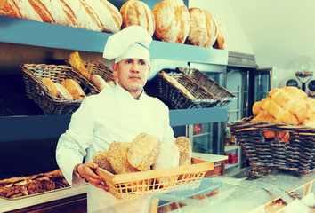 Middle aged baker is showing tasty bread