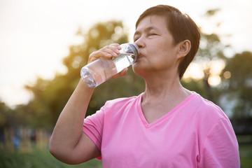 Asian senior Female drinking water.