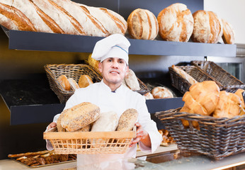 Male employee offering fresh baguettes and buns in bakery
