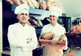 Male and female staff offering fresh baguettes