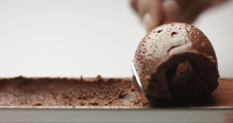 Soft spongy chocolate mousse taken out of a stainless steel pan with a teaspoon isolated on white