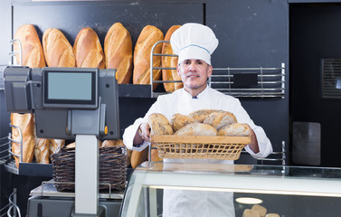 professional bakery male worker with tasty and fresh bread products on counter