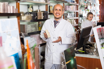 Two happy pharmacists standing next to shelves