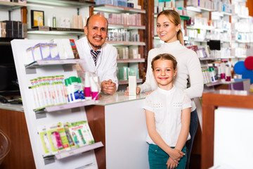 pharmacist standing with a cash desk