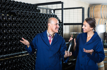 man and women winemakers with wine bottle.