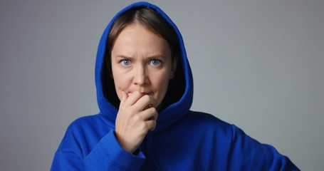 Young woman in large unlabeled bright blue hoodie screams and acts scared and angry showing stress