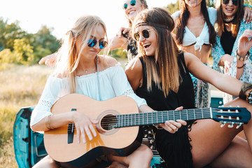 Girls are sitting on the trunk with a guitar