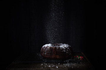 Chocolate bundt cake with powdered sugar on dark background.