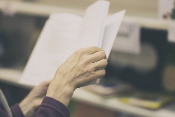 Close-up of hands of elderly person with open book, library. Toned background. Education concept, Self-study, reading fiction, pension, interests in elderly, life style