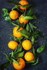 Fresh mandarin with leaves on darl stone background.