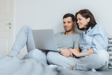 Happy couple in love review their wedding photos on laptop computer, remember plesant moments and special event in their life, use modern laptop computer and free internet connection at home