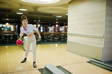 Girl with bowling ball on alley played at bowling club.