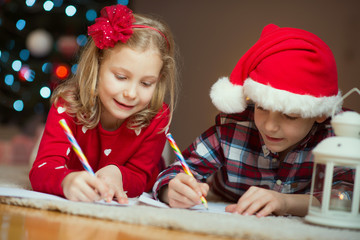 Two happy children writing letter to Santa Claus at home near New Year tree