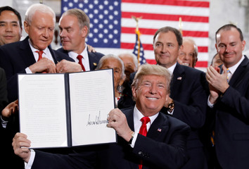 U.S. President Donald Trump smiles after signing an executive order after announcing big cuts to Utah's sprawling wilderness national monuments at the Utah State Capitol in Salt Lake City,
