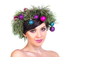 A beautiful woman in a wreath of Christmas tree branches and New Year's decoration on white background, isolate.