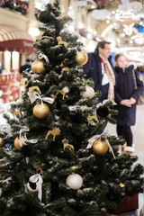 Photo of Christmas decorated New year tree with golden and white toys