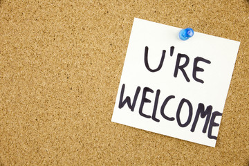 You Are wellcome sign written on sticky note pinned on pinboard