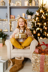 Photo of girl with gift in hands background of Christmas decorations in studio