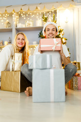 Image of man and woman in Santa cap with gift in box