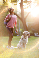 Picture of young brunette on walk with dog in summer park