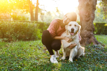 Image of woman hugging dog on lawn