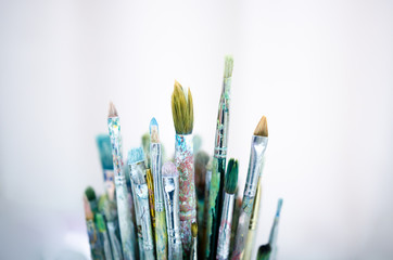 Various dirty paintbrushes on a gray background