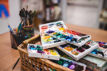 Set of watercolor paints in basket. Creative studio