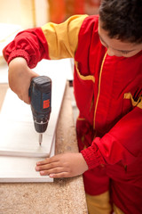 Young teenager boy working with drilling machine,concept of  future profession