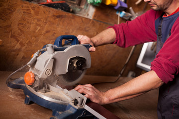 Skilled carpenter cutting a piece of wood in his woodwork workshop, using a circular saw