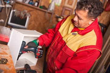 Carpenter working with an electric screwdriver on the work bench