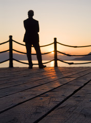 A man stands on the wooden quay of the Aegean Sea at sunset