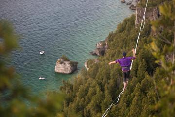 Man walking a high line slack line high above water