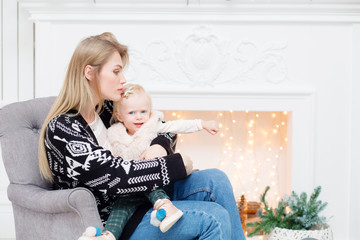 Christmas or New year celebration. Happy mother and daughter embracing. White fireplace on background