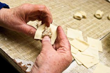 Old woman is making traditional dumplings