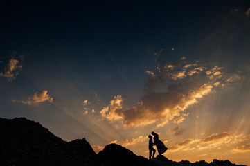 silhouette of a pregnant woman and men in nature