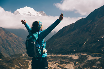 Standing young woman with backpack and raised up arms on the hill and looking on mountains. Landscape with happy girl, mountains, blue sky with clouds in autumn in Nepal. Travel. Trekking in Himalayas