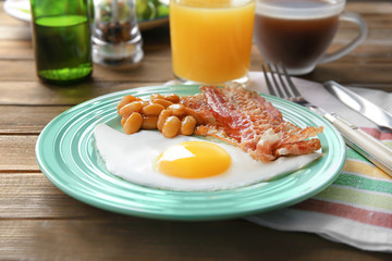 Plate with fried egg, bacon and beans on wooden table