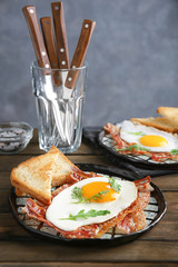 Plate with fried egg and bacon on wooden table