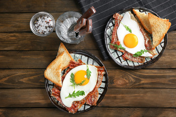 Plates with fried eggs and bacon on wooden table