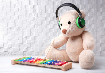 Toy with headphones on table against white wall. Baby songs concept