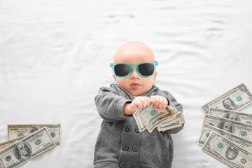 Cute boy with money on white bedsheet