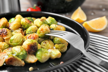 Plate with roasted brussel sprouts on table, closeup