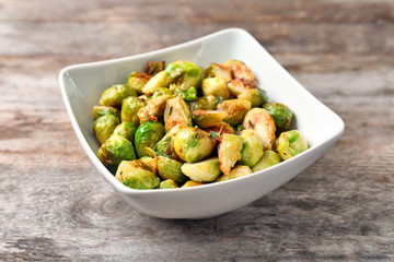 Bowl with roasted brussel sprouts on wooden background