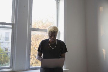 Young man uses his laptop on a window sill in his apartment