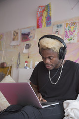 Young man in headphones on his laptop in bed