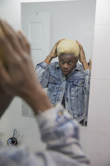 A young man fixing his hair in the bathroom