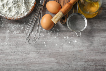 Composition with cooking utensils and ingredients on wooden background