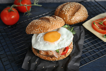 Tasty burger with prosciutto and egg on metal grid