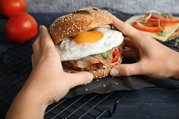 Woman holding tasty burger with prosciutto and egg at table